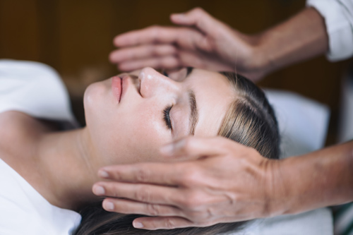 Reiki practitioner holding hands on both sides of clients head to transfer energy.